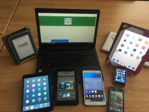 Collection of eReaders, tablets, and laptop.